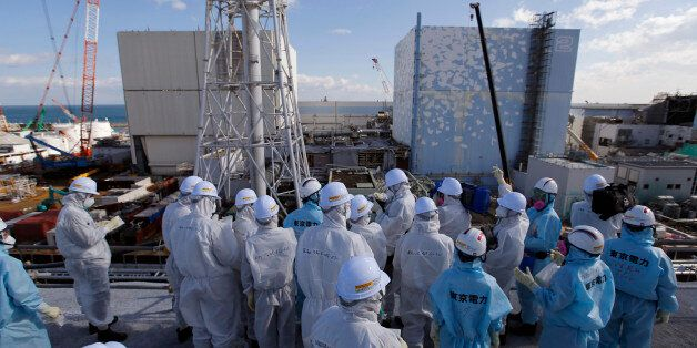 Members of the media tour group, wearing protective suits and masks, receive a briefing from Tokyo Electric...