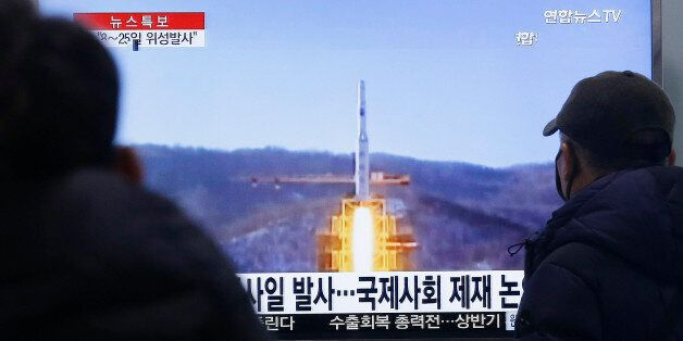 South Koreans watch a TV news program with a file footage about North Korea's rocket launch plans, at...