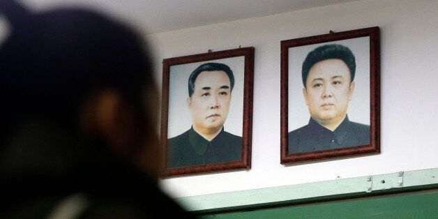 A visitor tours near the pictures of North Korean founder late Kim Il Sung, left, and his son, leader...