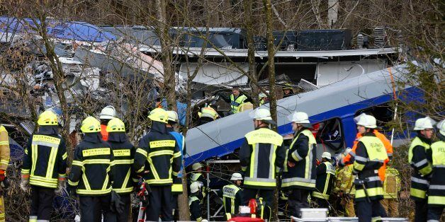 Rescue personnel stand in front of two trains that collided head-on near Bad Aibling, southern Germany,...