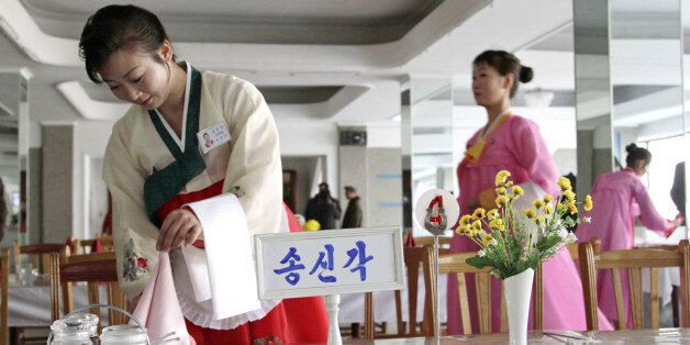 A North Korean waitress folds a napkin before the start of a cooking competition held at a noodle restaurant...