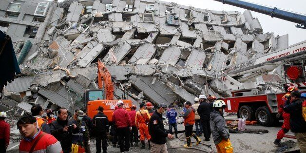 In this Saturday, Feb. 6, 2016 photo, rescue workers search a collapsed building from an early morning...