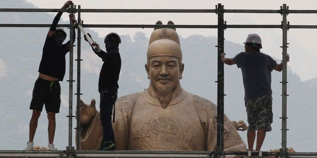 Construction workers set up a stage in front of a statue of Chosun Dynasty's King Sejong for public viewing...