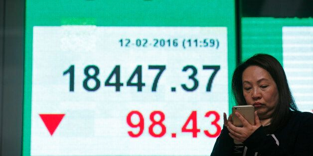 A woman uses her smartphone in front of an electronic board showing the Hong Kong index at a bank in...