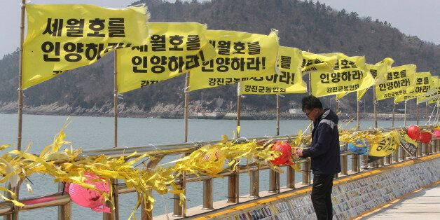 An unidentified man reads messages tied with yellow ribbons for the victims of the sunken ferry Sewol...