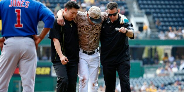 Pittsburgh Pirates' Jung Ho Kang, center, is helped off the field by team trainer, right, and his interpreter...