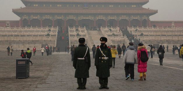 Chinese paramilitary policemen stand guard in the Forbidden City during a smoggy day in Beijing, China,...