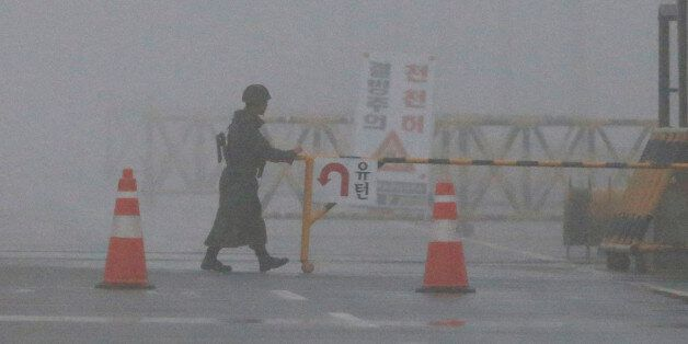 A South Korean Army soldier adjusts barricade on a foggy and rainy morning at Unification Bridge near...