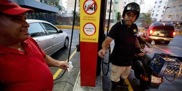 A motorcyclist pays about two Bolivars (3 cents of a dollar) after filling his scooter's tank at a gas...