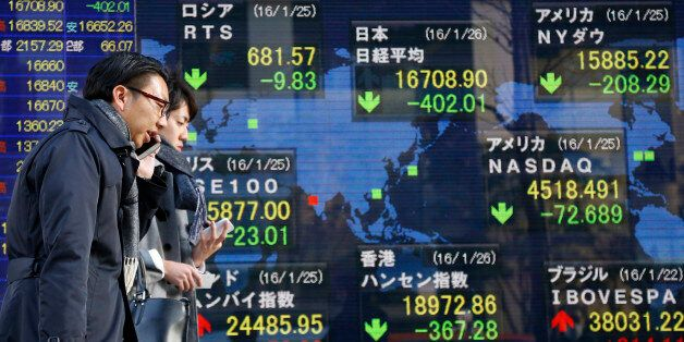 People walk past an electronic stock indicator of a securities firm showing global stock shares including...
