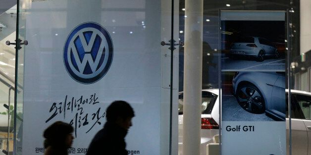 People walk by a logo of Volkswagen at a dealership in Seoul, South Korea, Thursday, Nov. 26, 2015. South...