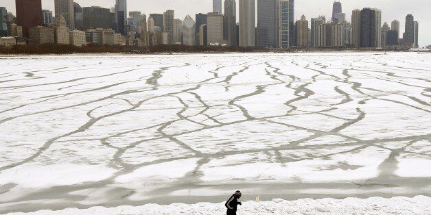 A lone jogger runs in the snow near the Adler Planetarium and Monroe Harbor on Lake Michigan Friday,...