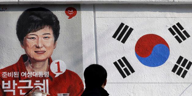 A man looks at the wall paintings of South Korea's President-elect Park Geun-hye of ruling Saenuri Party...