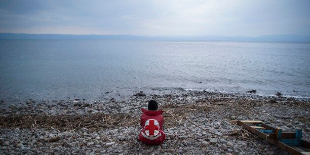 A member of the Greek Red Cross waits for migrants and refugees to arrive on a beach of the Greek island...