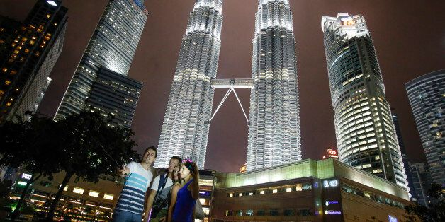 Tourists take souvenir photographs against Malaysia's iconic building, Petronas Twin Towers in Kuala...