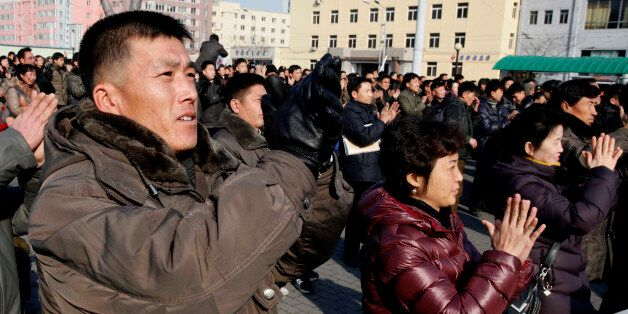 North Koreans watch a news broadcast on a video screen outside Pyongyang Railway Station in Pyongyang,...