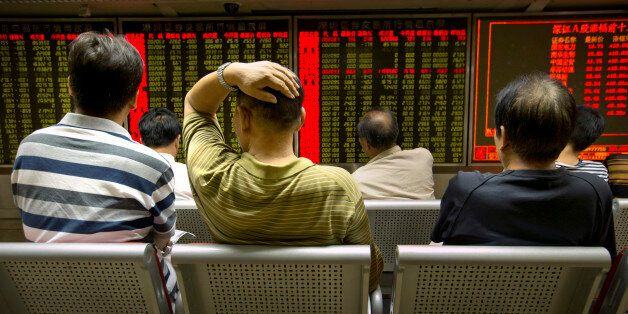 Chinese investors monitor stock prices at a brokerage house in Beijing, Tuesday, Aug. 18, 2015. The Shanghai...