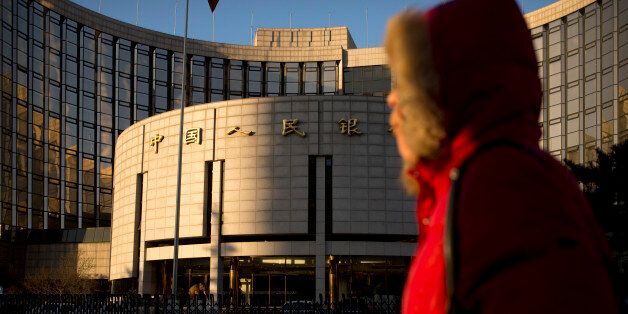 In this Friday, Jan. 8, 2016 photo, a woman walks past China's central bank, the People's Bank of China,...