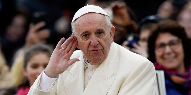 Pope Francis puts his hand to his ear to listen to a musical band playing as he arrives on his popemobile...