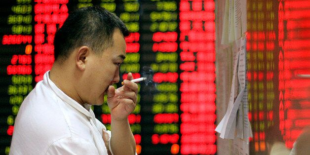 An investor checks market news on a board at a private security company Wednesday, April 9, 2008 in Shanghai,...