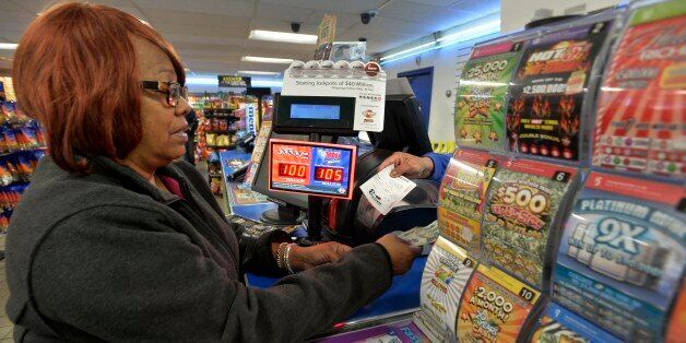 In this Oct. 23, 2015 photo, Vera Washington of Chicago, buys lotto tickets at the K&D Marathon station...
