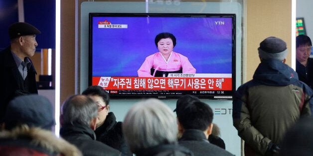 People watch a TV news program showing North Korea's announcement, at the Seoul Railway Station in Seoul,...