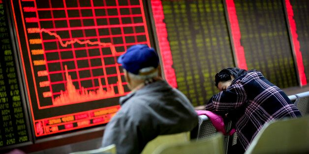 A woman takes a nap as a man looks at an electronic board displaying stock prices at a brokerage house...