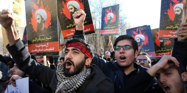 Iranian demonstrators chant slogans during a protest against the execution of Sheikh Nimr al-Nimr, shown...