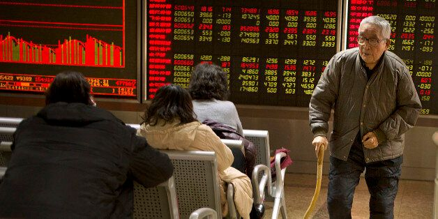 A Chinese investor walks through a brokerage house in Beijing, Friday, Dec. 4, 2015. Asian stocks sank...