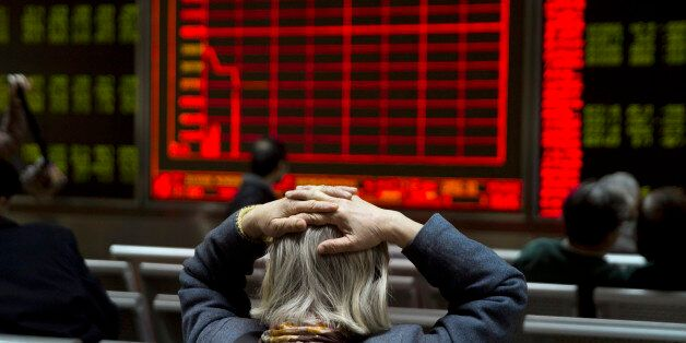 A woman reacts near a display board showing the plunge in the Shanghai Composite Index at a brokerage...