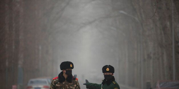 Chinese paramilitary policemen stop a car from entering a blocked-off road in an embassy district in...