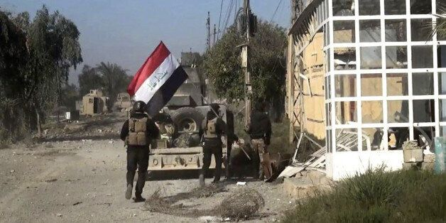 Iraqi security forces hold a national flag as they enter the southern neighborhoods of Ramadi, 70 miles...