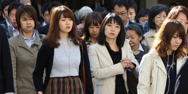 In this Monday, Oct. 26, 2015 photo, commuters cross a street during morning rush hour in Tokyo. The...