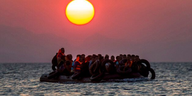 FOR USE AS DESIRED, YEAR END PHOTOS - FILE - Migrants on a dinghy arrives at the southeastern island...
