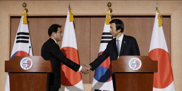 South Korean Foreign Minister Yun Byung-se, right, shakes hands with his Japanese counterpart Fumio Kishida...