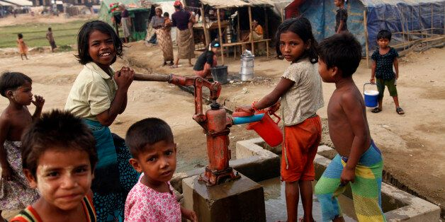 In this photo taken on April 2, 2014, Muslim refugee children gather at a tube-well to fetch water near...