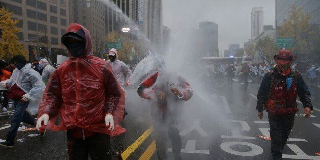 South Korean riot police officers spray water cannons to try to break up protesters who tried to march...