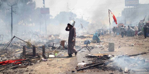 A supporter of Egypt's ousted president Mohamed Morsi walks through the debris following clashes with...