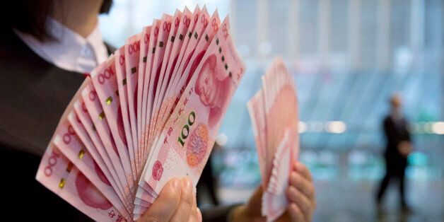 A staff member displays the new version of the 100-yuan RMB banknotes for photographers at the Bank of...