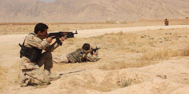Afghanistan's security forces take their position during a clash by Taliban fighters in the highway between...