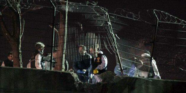 Police forensic officers investigate after an explosion on a highway overpass near a subway station wounded...