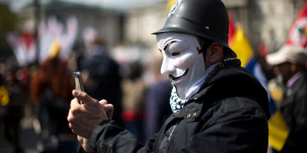 A protester wearing a toy British police helmet and an Anonymous mask takes a picture during a rally...