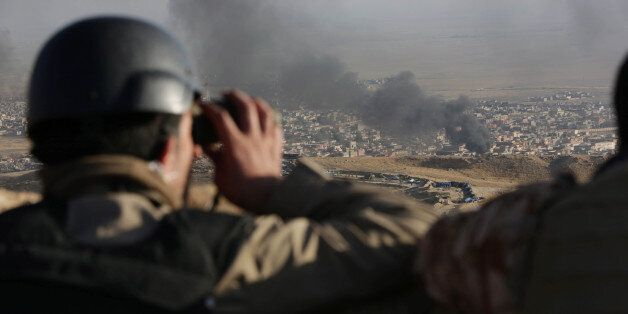 A journalist watches as smoke rises over Sinjar, northern Iraq from oil fires set by Islamic State militants...