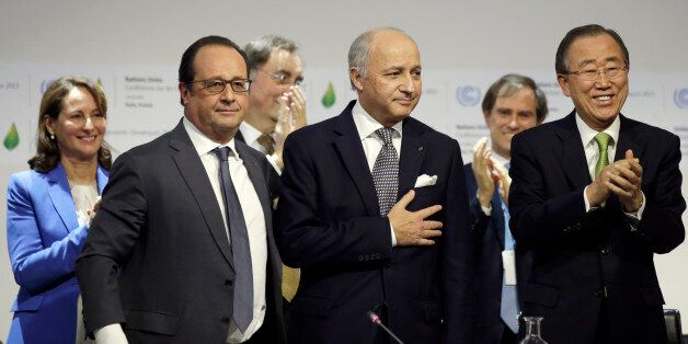 French Foreign Affairs Minister Laurent Fabius, center, President-designate of COP21, puts his hand over...