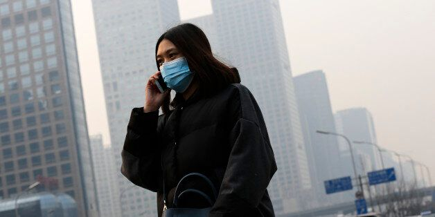A woman wearing a mask to protect herself from pollutants walks past office buildings shrouded with pollution...