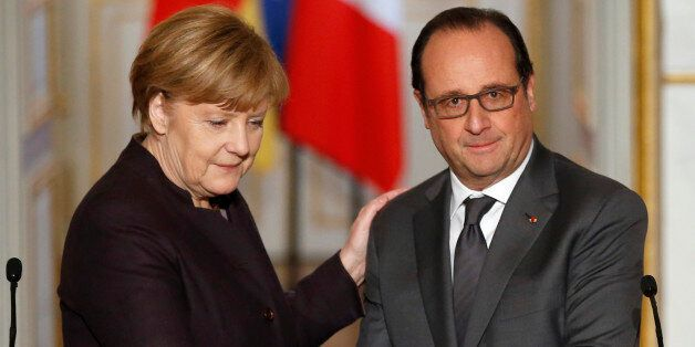 French president Francois Hollande, right, shakes hands with German Chancellor Angela Merkel at the end...