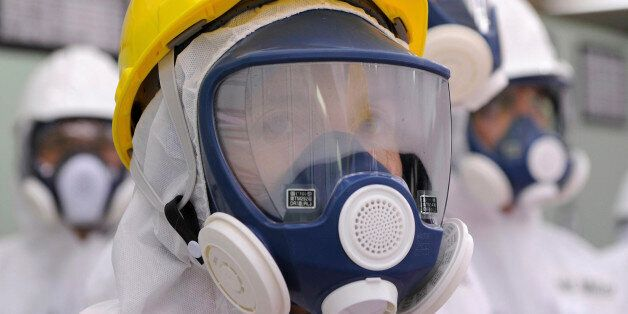 U.S. Ambassador to Japan Caroline Kennedy wearing a yellow helmet and a mask inspects the central control...