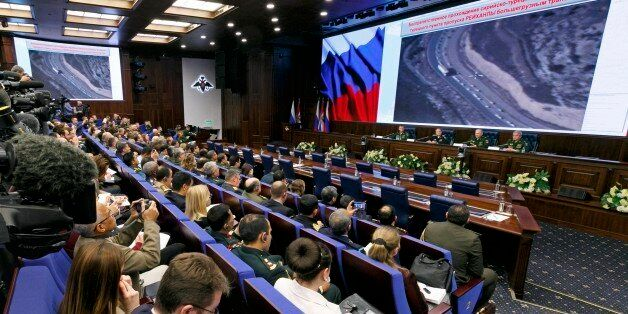 Russian top military officials speak to the media in front of an aerial images of what they say are oil...