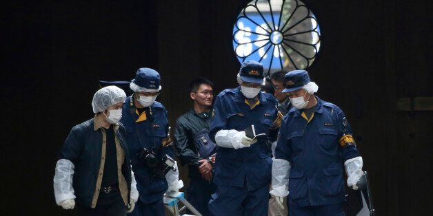Police officers investigate the compound of Yasukuni shrine following an explosion in its public restroom...