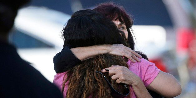 Teresa Hernandez, facing camera, is comforted by a woman as she arrives at a social services center in...